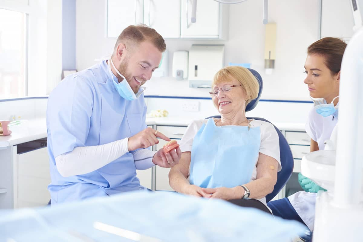 A Dentist Talking to a Patient About Affordable Dentures